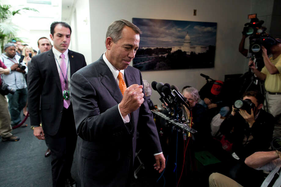 Speaker of the House Rep. John Boehner, R-Ohio, pumps his fist as he walks past reporters after a meeting with House Republicans on Capitol Hill on Wednesday, Oct. 16, 2013 in Washington. The partial government shutdown is in its third week and less than two days before the Treasury Department says it will be unable to borrow and will rely on a cash cushion to pay the country's bills. (AP Photo/ Evan Vucci) / AP