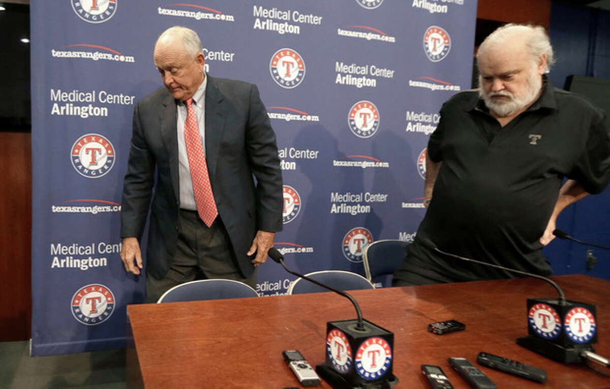 Texas Rangers CEO and President Nolan Ryan, left, and team owner Bob Simpson stand up after a news conference announcing Ryan's retirement from the baseball team in Arlington, Texas, Thursday, Oct. 17, 2013. Ryan is retiring at the end of the month after six seasons as CEO. (AP Photo/LM Otero)