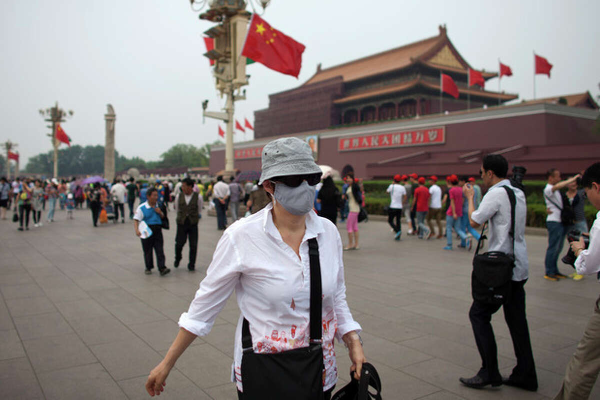 FILE - This is a May 7, 2013 file photo of a foreign tourist wearing a mask walks in front of Tiananmen Gate on a polluted day in Beijing, China. What many commuters choking on smog have long suspected has finally been scientifically validated: air pollution causes lung cancer. The International Agency for Research on Cancer declared on Thursday that air pollution is a carcinogen, alongside known dangers such as asbestos, tobacco and ultraviolet radiation. (AP Photo/Alexander F. Yuan, File)