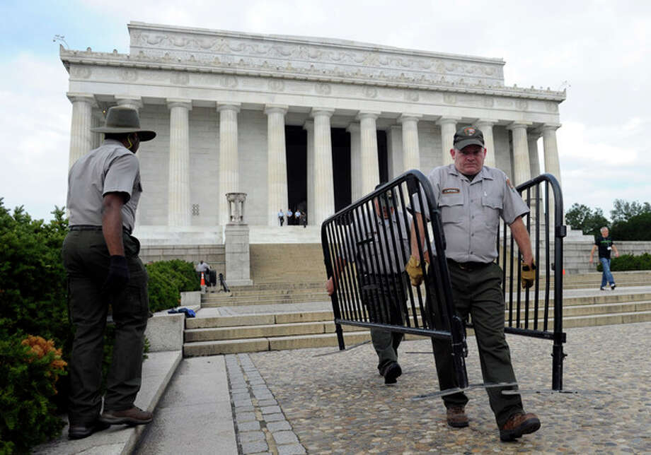 National Park Service employee James Mitchell, right, and others, remove barricades from the grounds of the Lincoln Memorial in Washington, Thursday, Oct. 17, 2013. Barriers went down at National Park Service sites and thousands of furloughed federal workers began returning to work throughout the country Thursday after 16 days off the job because of the partial government shutdown.(AP Photo/Susan Walsh) / AP