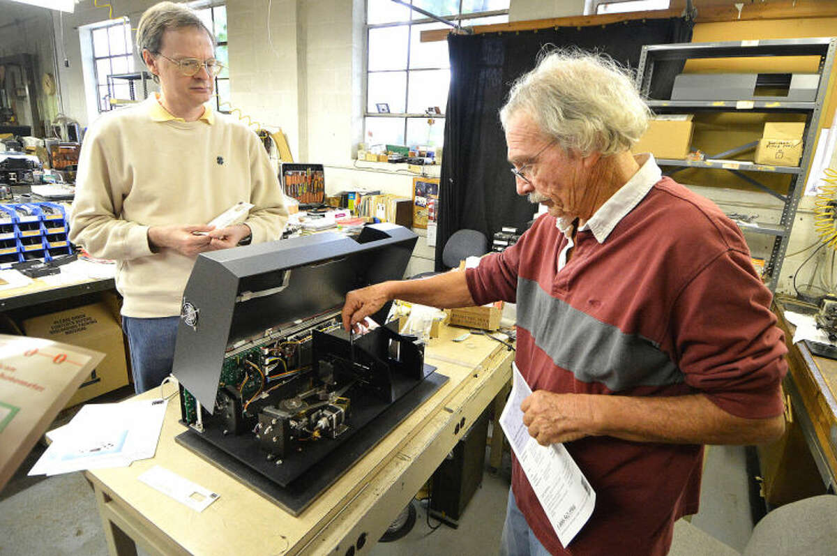 Hour Photo/Alex von Kleydorff . Derek Hodgeman and owner Bob Anderson open the case of one of their Quick Scan Infrared Spectophotometer on the production line at Buck Scientific in Norwalk