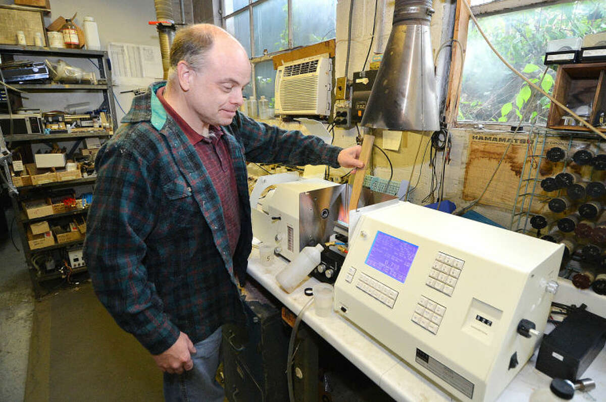 Hour Photo/Alex von Kleydorff. Production Manager John Mellor makes an adjustment for sampling base materials during final set up of one of the new Atomic Absorption Spectophotometer at Buck Scientific in Norwalk