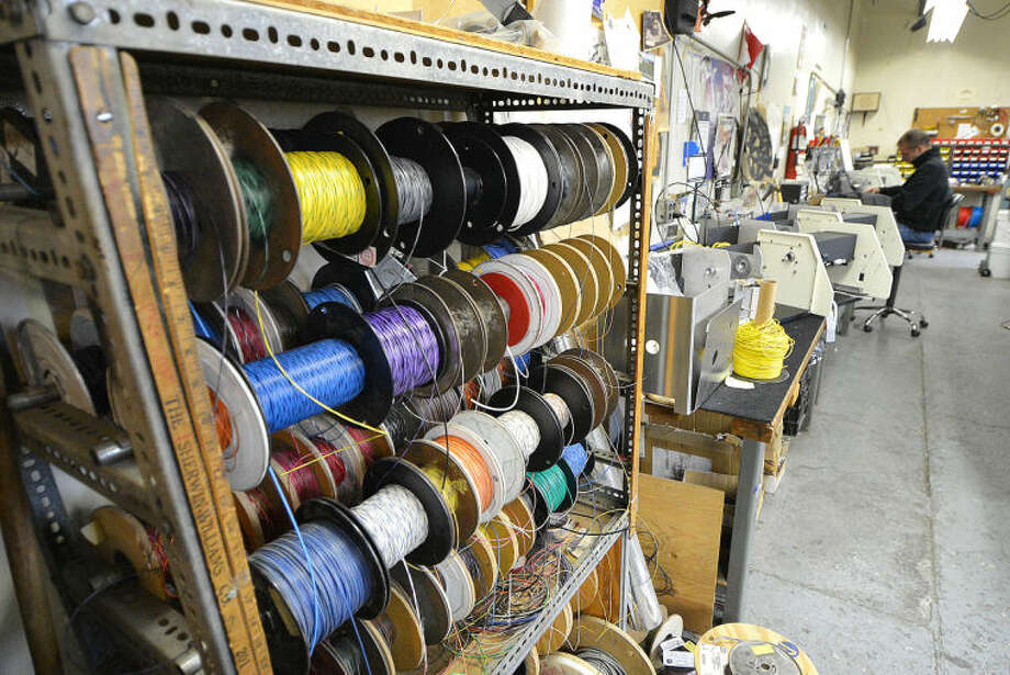Hour Photo/Alex von Kleydorff . A rack of color coded wire hangs within easy reach of workbenches at Buck Scientific
