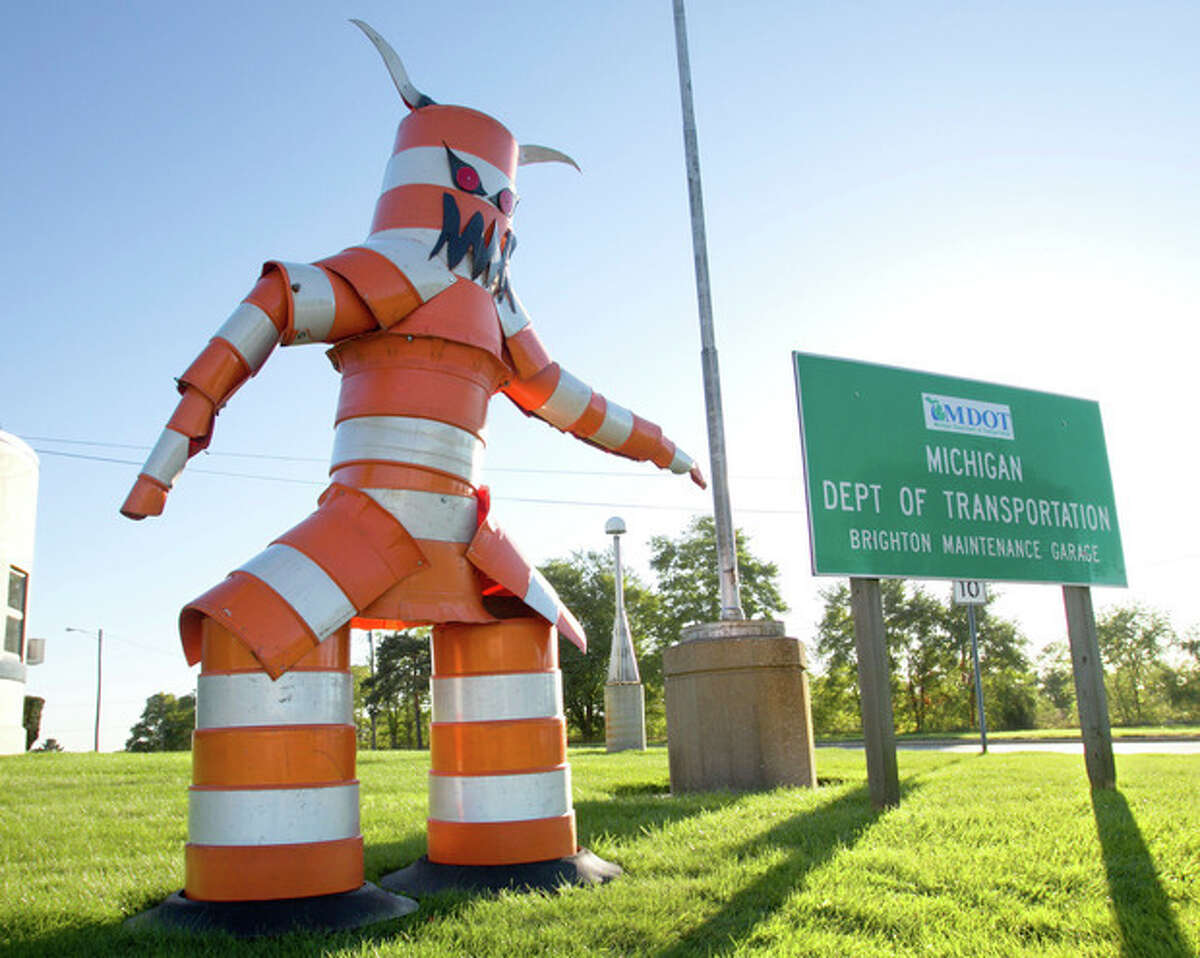 A monster constructed from traffic cones by garage workers looms over drivers passing along Grand River near Old U.S. 23 in front of the MDOT Brighton Maintenance Garage, Thursday, Oct. 10, 2013. (AP Photo/Livingston County Daily Press & Argus, Gillis Benedict)