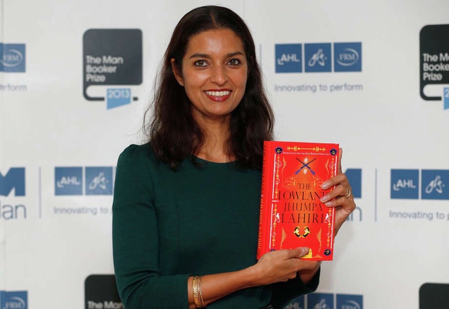 FILE - In this Oct. 13, 2013 file photo, author Jhumpa Lahiri poses with her book 'The Lowland' in London. Lahiri, Thomas Pynchon, and George Saunders were among the finalists Wednesday, Oct. 16, 2013 for the National Book Awards. A month after releasing long-lists of 10 in each of the four competitive categories, the National Book Foundation announced the five remaining writers for fiction, nonfiction, poetry and young people's literature. Winners receive $10,000 and will be announced at a dinner ceremony in Manhattan on Nov. 20. (AP Photo/Sang Tan) / AP