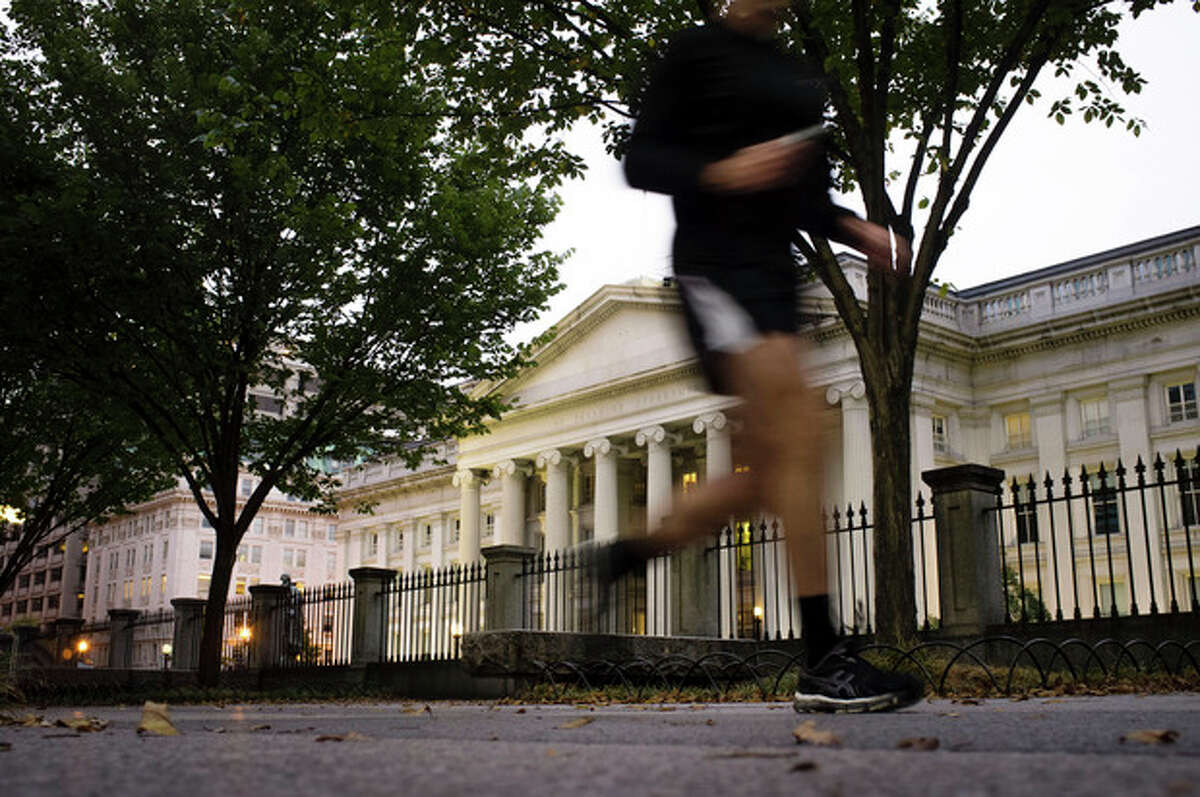 A jogger on an early morning run passes the U.S Treasury Building in Washington, Wednesday, Oct. 16, 2013, a day before the stalemate in Congress over the budget could cause the government to reach its borrowing limit. (AP Photo/J. David Ake)