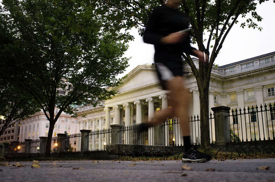 A jogger on an early morning run passes the U.S Treasury Building in Washington, Wednesday, Oct. 16, 2013, a day before the stalemate in Congress over the budget could cause the government to reach its borrowing limit. (AP Photo/J. David Ake) / AP