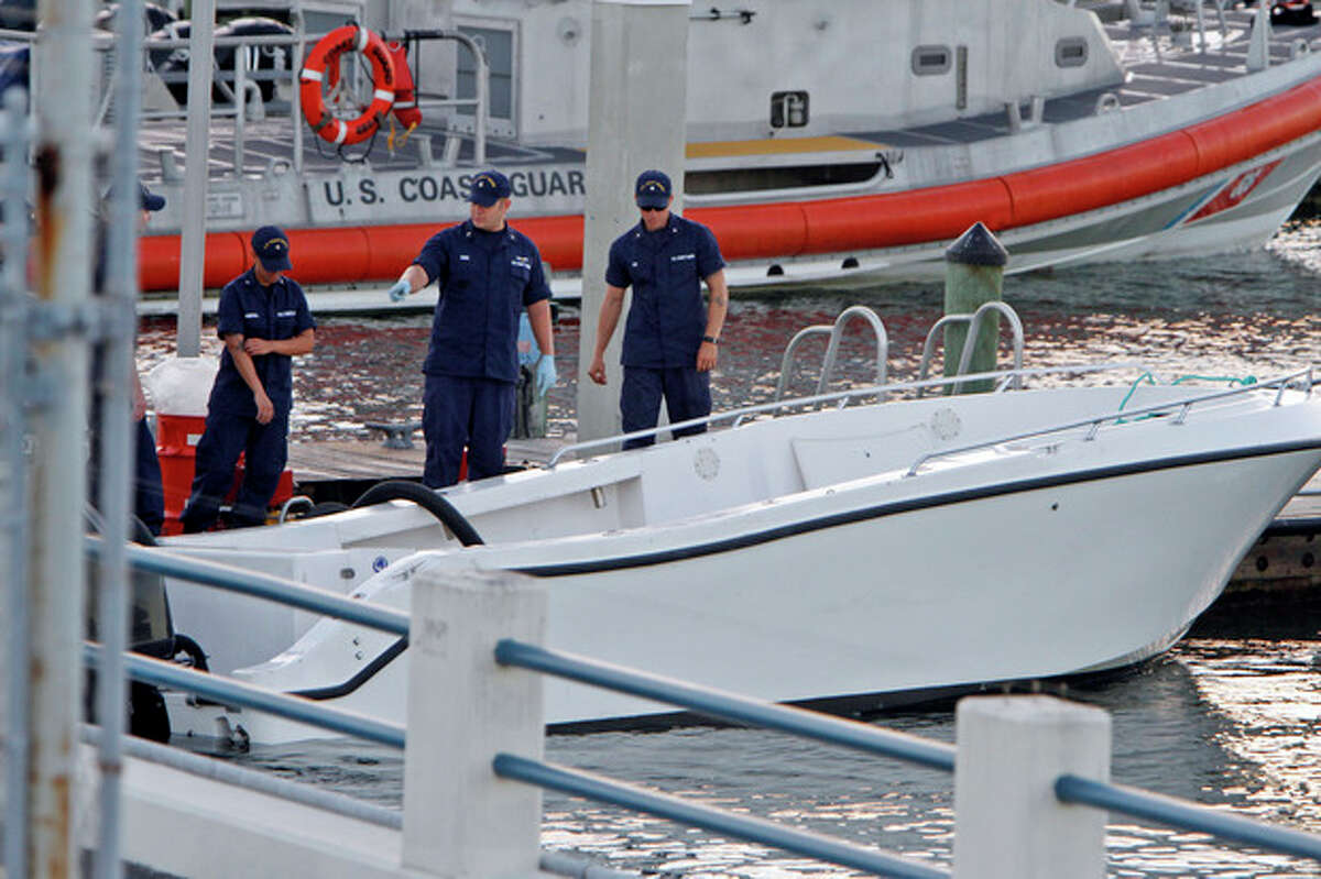 U.S Coast Guard personnel inspects a vessel with a missing center console that capsized near Miami, Wednesday Oct. 16, 2013. The Coast Guard responded to an early morning call and found nine people clinging to the hull seven miles east of Miami. Four women died and 10 other people were taken into custody after the boat with more than a dozen people aboard, including Haitian and Jamaican nationals, capsized in the waters off South Florida. Authorities are investigating whether the victims and survivors were part of a human smuggling operation. (AP Photo/Miami Herald, Walter Michot) NO MAGS
