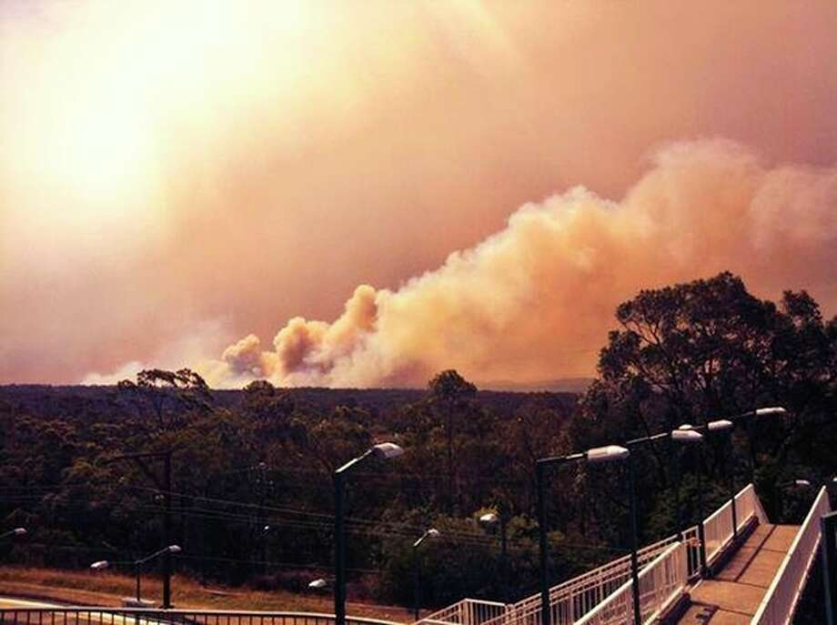 In this photo provided by the New South Wales Rural Fire Service, smoke rises from a fire near Springwood, west of Sydney, Thursday, Oct. 17, 2013. Nearly a hundred wildfires are burning across Australia's New South Wales state, more than a dozen of which are out of control, as unseasonably hot temperatures and strong winds fanned flames across the parched landscape. (AP Photo/New South Wales Rural Fire Service) / New South Wales Rural Fire Service