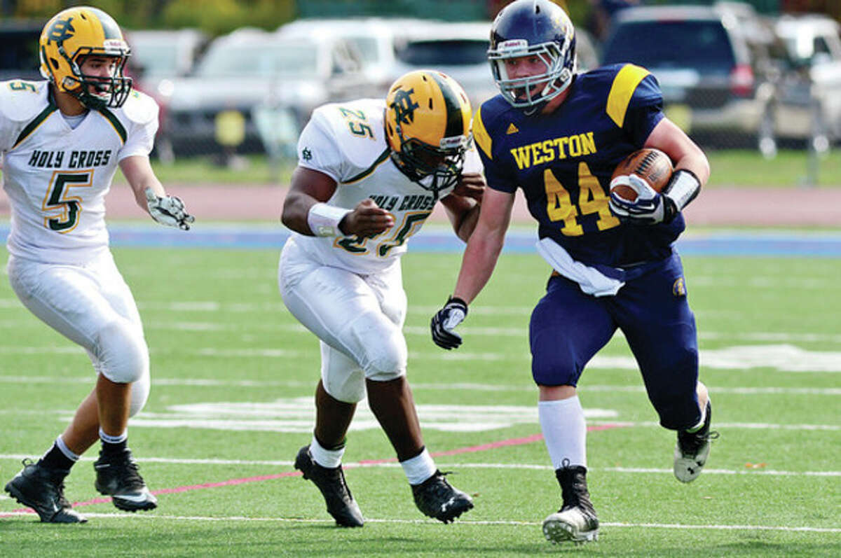Hour photo/Erik Trautmann Weston running back Peter Lummis, right, looks for room to manuever as Gerron Pendarvis of Holy Cross closes in during Saturday afternoon's game in Weston. The visiting Crusaders saddled the Trojans with a 37-7 defeat.