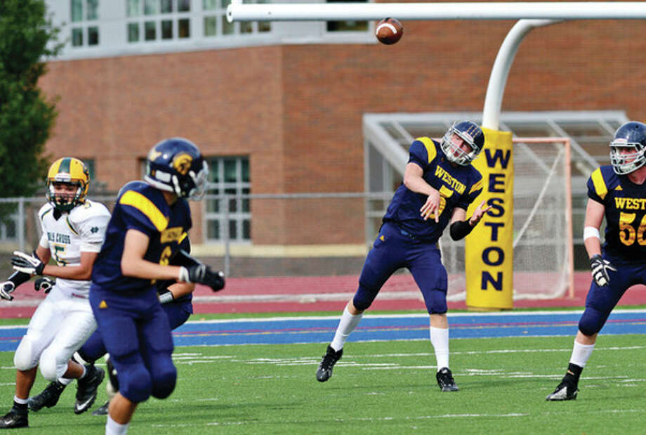 Hour photo/Erik TrautmannWeston's quarterback Erik Dammen-Brower unleashes a pass during Saturday's game against Holy Cross. / (C)2013, The Hour Newspapers, all rights reserved