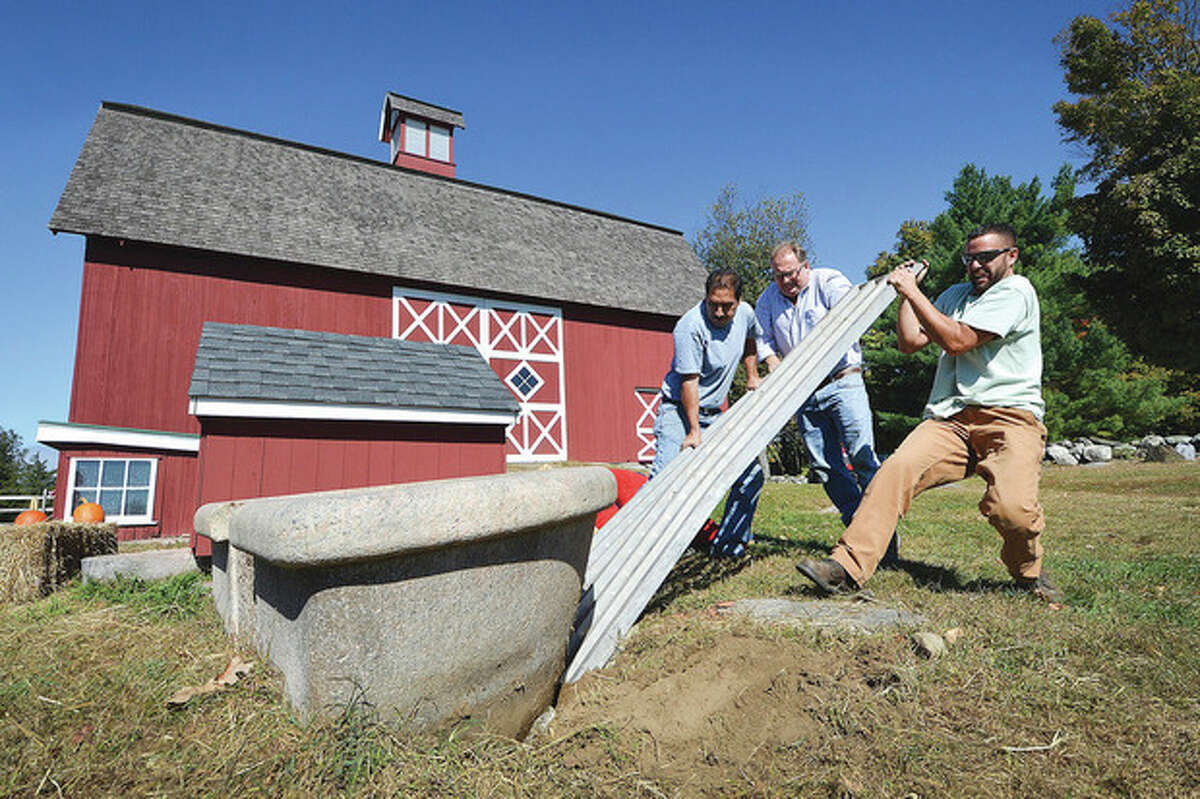 Hour Photo/Alex von Kleydorff At Wilton's Ambler farm, Norwalk Parks Dept. Supervisor Ken Hughes along with Jordan Grant and Freddy Cardona get started using aluminum wheel ramps to loosen the fountain and raise it out of the ground for moving to Norwalk