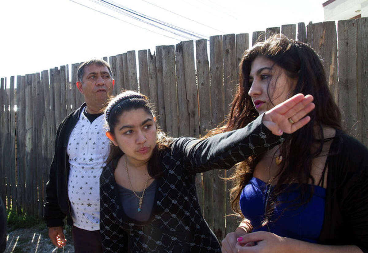 Leonarda Dibrani, 15, center, with her sister Maria, 17, and her father Resat Dibrani gestures in front of a shelter house in the northern town of Mitrovica, Kosovo on Friday Oct. 18, 2013. The family were expelled from France as illegal immigrants last week and Leonarda Dibrani, taken by police from a school field trip last week, shocked many. Thousands of high school students protested in Paris angry at the expulsion of immigrant children and families like the Dibrani family. The demonstration came as the government was finalising a report on Friday into the treatment of a 15-year-old girl taken by police from a school field trip, then deported to Kosovo with her family as illegal immigrants. (AP Photo/Visar Kryeziu)