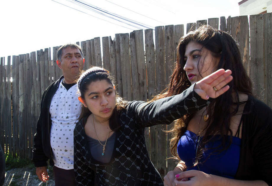 Leonarda Dibrani, 15, center, with her sister Maria, 17, and her father Resat Dibrani gestures in front of a shelter house in the northern town of Mitrovica, Kosovo on Friday Oct. 18, 2013. The family were expelled from France as illegal immigrants last week and Leonarda Dibrani, taken by police from a school field trip last week, shocked many. Thousands of high school students protested in Paris angry at the expulsion of immigrant children and families like the Dibrani family. The demonstration came as the government was finalising a report on Friday into the treatment of a 15-year-old girl taken by police from a school field trip, then deported to Kosovo with her family as illegal immigrants. (AP Photo/Visar Kryeziu) / AP