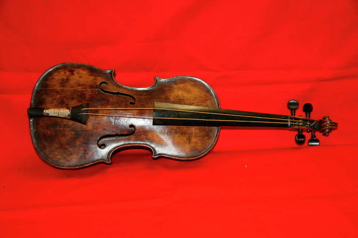 """This is an undated handout image from auction house Henry Aldridge and Son made available on Friday Oct. 18, 2013 shows a violin believed to be the one played by Titanic bandmaster Wallace Hartley will now go on auction. It?'s a poignant scene familiar to anyone who has watched ?""""Titanic?"""" as the ship slides into the icy waters, musicians perform for the passengers, playing with stoic resolve until the final hour. None of the musicians survived in the 1912 disaster in the North Atlantic. The auction house, which specializes in Titanic memorabilia, expects the violin to fetch more than 200,000 pounds (US$323,300) when it goes on sale Saturday Oct 19, 2013. (AP Photo/Henry Aldridge and Son)"""