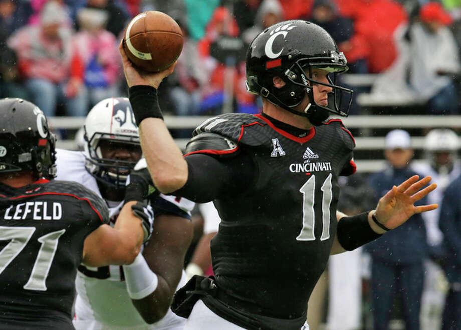Cincinnati quarterback Brendon Kay (11) passes against Connecticut in the first half of an NCAA college football game, Saturday, Oct. 19, 2013, in Cincinnati. (AP Photo/Al Behrman) / AP