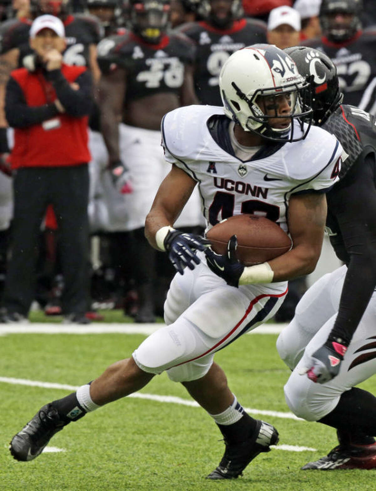 Connecticut running back Lyle McCombs (43) is pursued by Cincinnati linebacker Greg Blair in the first half of an NCAA college football game, Saturday, Oct. 19, 2013, in Cincinnati. (AP Photo/Al Behrman)