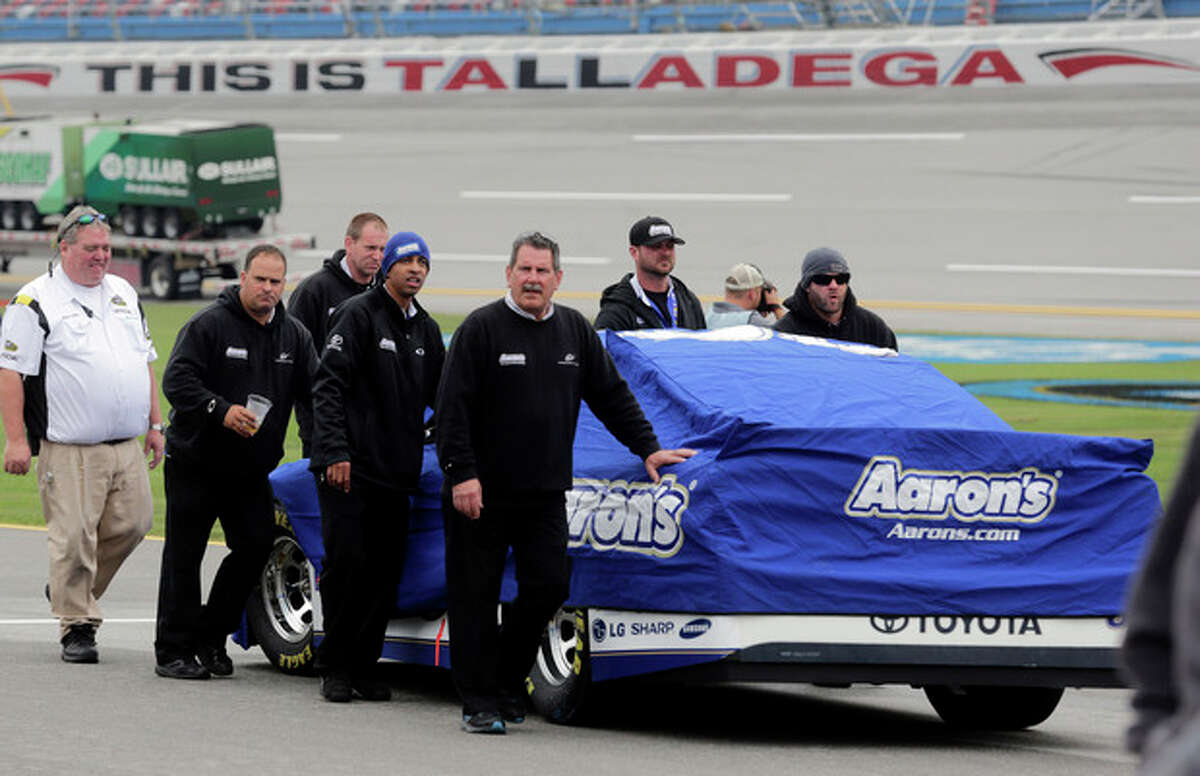 Pit crew members push the car of Michael Waltrip back to the garage area after rain showers caused Sprint Cup qualifying to be canceled for Sunday's NASCAR Sprint Cup Series auto race at Talladega Superspeedway in Talladega, Ala., Saturday, Oct. 19, 2013. The field will start based on their Friday practice speeds. (AP Photo/Jay Sailors)