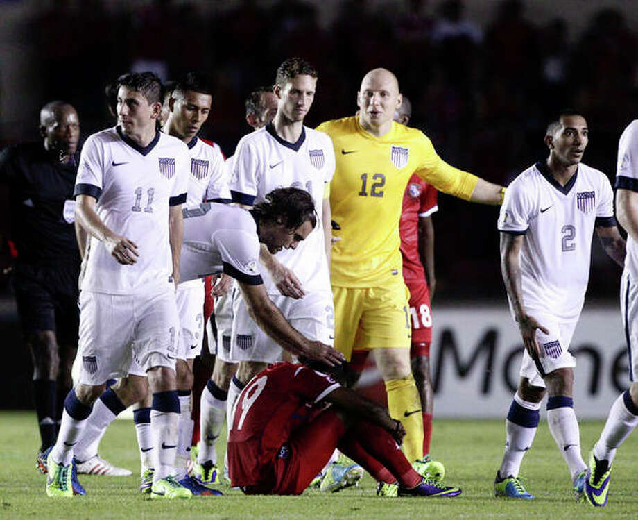 Graham Zusi of the U.S. reaches out to a dejected Alberto Quintero of Panama after the U.S. defeated Panama in a 2014 World Cup qualifying soccer match in Panama City, Tuesday, Oct. 15, 2013. The United States rallied for a 3-2 win at Panama on Tuesday night that left Mexico's World Cup hopes alive and knocked out the Panamanians. (AP Photo/Arnulfo Franco) / AP