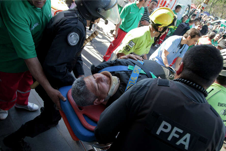 Police officers and paramedics carry a wounded passenger to an ambulance after a commuter train slammed into the end of the line when arriving to Once central station early this morning in Buenos Aires, Argentina, Saturday, Oct. 19, 2013. Paramedics rescued scores of wounded commuters. According to Security Secretary Sergio Berni, they are still evacuating the wrecked train, making that impossible to say immediately why the train failed to stop, crashing through the bumper at the end of the line. (AP Photo/Eduardo Di Baia) / AP