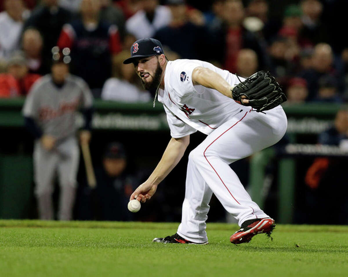Boston Red Sox relief pitcher Brandon Workman (67) bobbles a grounder by Detroit Tigers' Torii Hunter in the seventh inning during Game 6 of the American League baseball championship series on Saturday, Oct. 19, 2013, in Boston. (AP Photo/Charles Krupa)