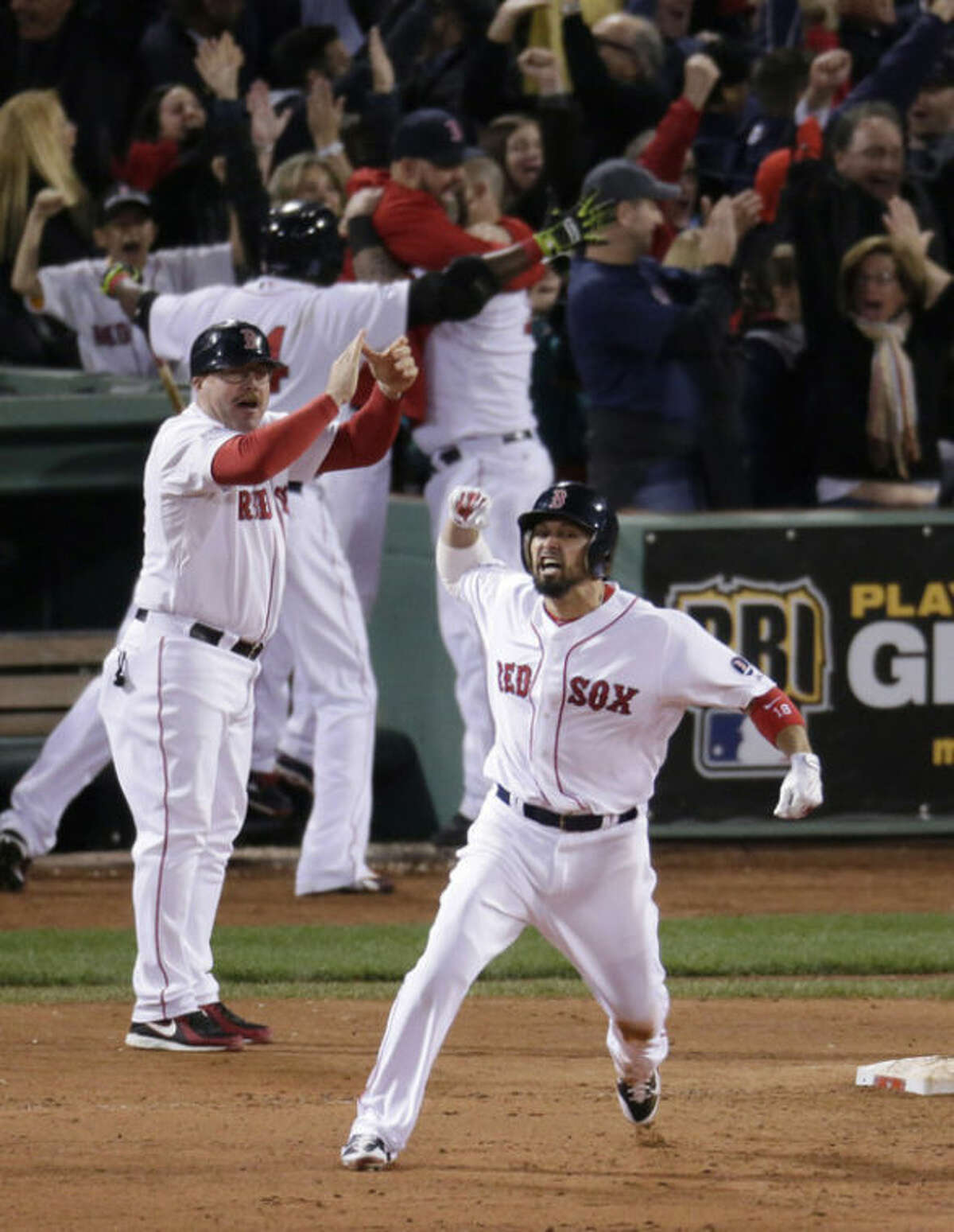 Boston Red Sox's Shane Victorino, front, celebrates his grand slam against the Detroit Tigers as he rounds first base in the seventh inning during Game 6 of the American League baseball championship series on Saturday, Oct. 19, 2013, in Boston. (AP Photo/Charlie Riedel)