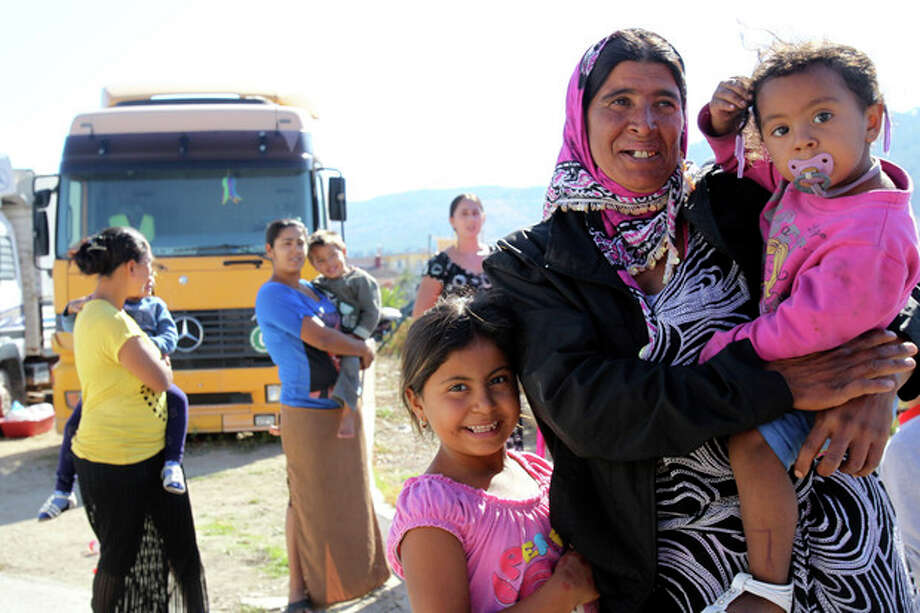 A gypsy woman holding her child poses for photos at a gypsy camp near the town of Farsala, some 280 km ( 173 miles) north of Athens, Greece, on Sunday, Oct. 20 , 2013. Greek authorities on Friday, Oct. 18, 2013 have requested international assistance to identify the four-year-old girl found living in a Gypsy camp with a couple arrested and charged with abducting her from her birth parents. A police statement says the child was located Wednesday, Oct. 17, 2013 near the town of Farsala, central Greece, during a nationwide crackdown on illegal activities in Gypsy camps. (AP Photo/Nikolas Giakoumidis) / AP