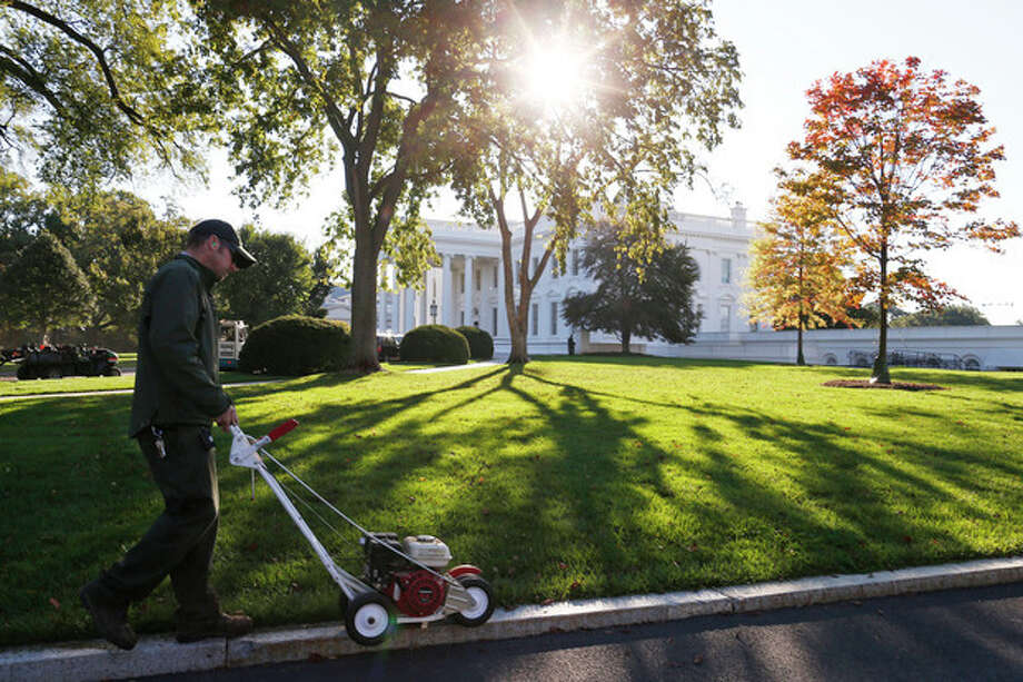 A National Park Service employee uses an edge trimmer as workers tend to the North Lawn of the White House in Washington, Friday, Oct. 18, 2013, after a 16-day partial government shutdown was resolved by lawmakers late Wednesday. (AP Photo/Charles Dharapak) / AP