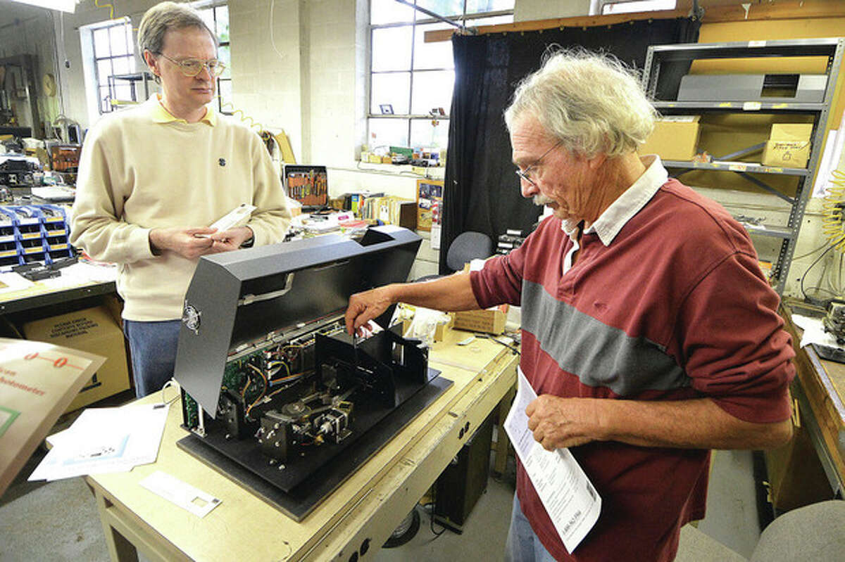 Hour Photo/Alex von Kleydorff Derek Hodgeman and owner Bob Anderson open the case of one of their Quick Scan Infrared Spectophotometer on the production line at Buck Scientific in Norwalk.