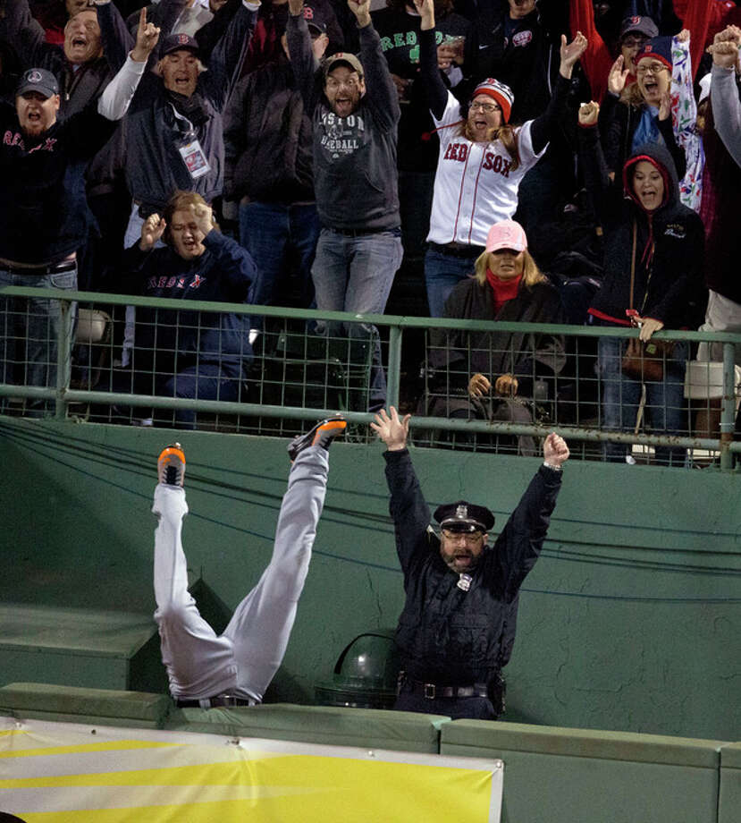 In this Oct. 13, 2013 photo, fans and Boston Police officer Steve Horgan celebrate as Detroit Tigers' Torii Hunter falls over the right field fence into the bullpen trying to catch a grand slam hit by Boston Red Sox' David Ortiz during Game 2 of the American League baseball championship series, in Boston. With one swing, Ortiz tied the game and helped the Red Sox send the AL championship series to Detroit tied one game apiece. (AP Photo/The Boston Globe, Stan Grosfeld) BOSTON HERALD OUT, QUINCY OUT; NO SALES INTERNET OUT ARCHIVE OUT / The Boston Globe