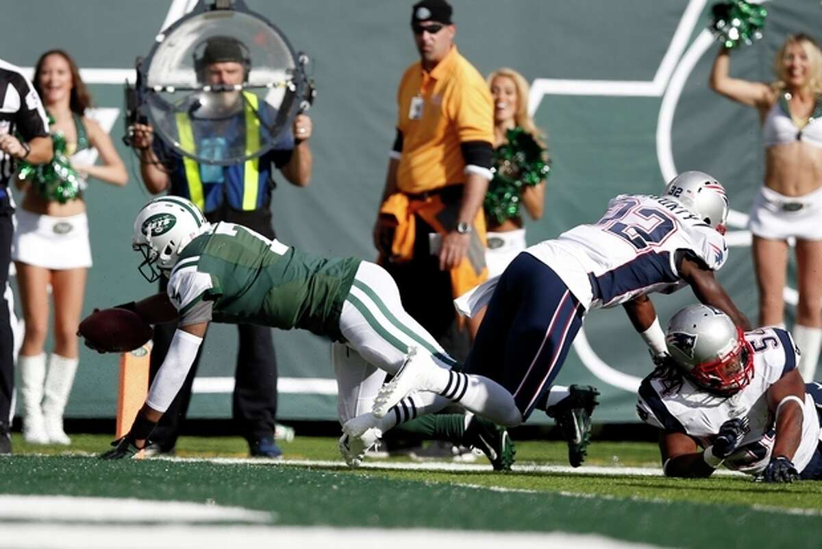New York Jets quarterback Geno Smith (7) dives for a touchdown as New England Patriots' Devin McCourty (32) and Dont'a Hightower, right, miss tackles during the second half of an NFL football game Sunday, Oct. 20, 2013, in East Rutherford, N.J. (AP Photo/Kathy Willens)