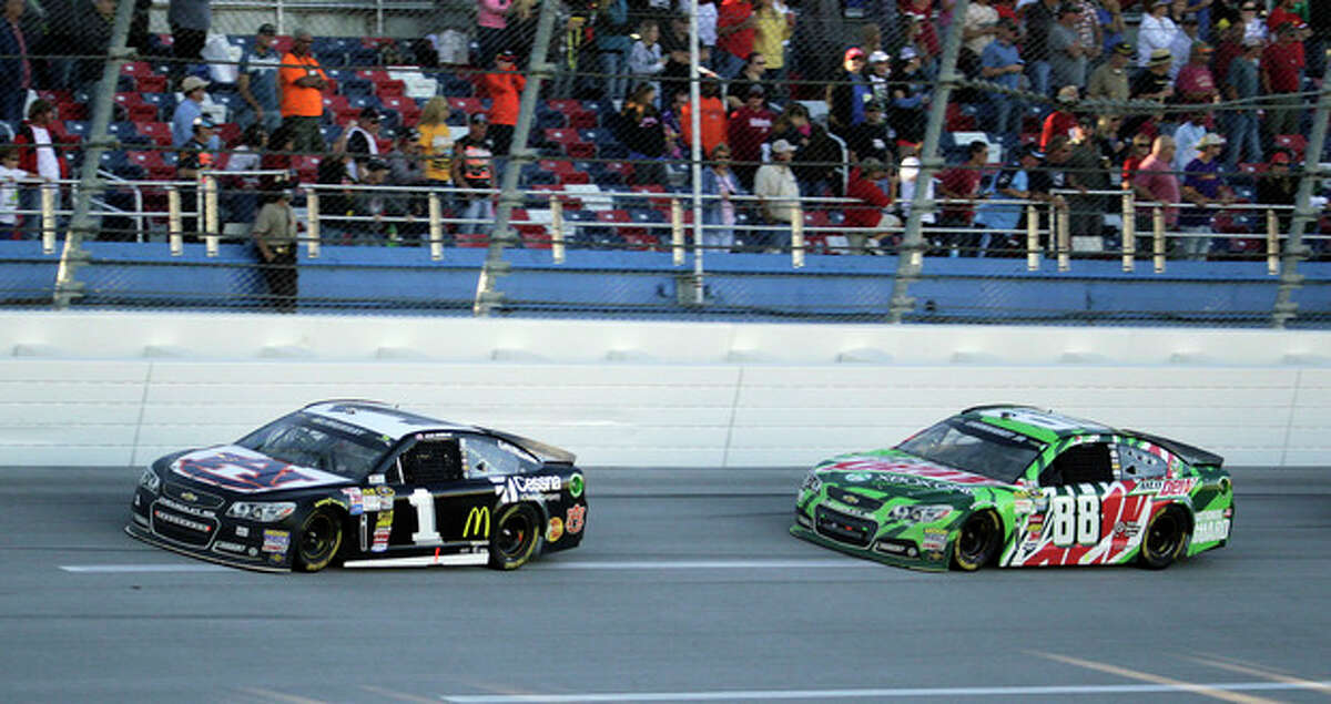 Sprint Cup Series driver Dale Earnhardt Jr. (88) follows driver Jamie McMurray (1) through the tri-oval during the NASCAR Sprint Cup Series auto race at the Talladega Superspeedway in Talladega, Ala., Sunday, Oct. 20, 2013. Earnhardt was runner-up for the fourth time this year, Sunday at Talladega Superspeedway, finishing behind Jamie McMurray. The race finished under caution after a last-lap crash. (AP Photo/Jay Sailors)