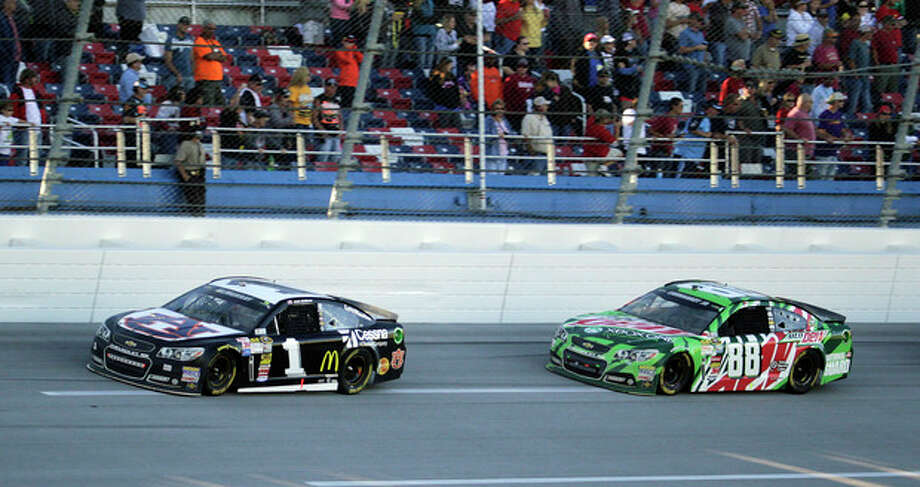 Sprint Cup Series driver Dale Earnhardt Jr. (88) follows driver Jamie McMurray (1) through the tri-oval during the NASCAR Sprint Cup Series auto race at the Talladega Superspeedway in Talladega, Ala., Sunday, Oct. 20, 2013. Earnhardt was runner-up for the fourth time this year, Sunday at Talladega Superspeedway, finishing behind Jamie McMurray. The race finished under caution after a last-lap crash. (AP Photo/Jay Sailors) / FR170137 AP