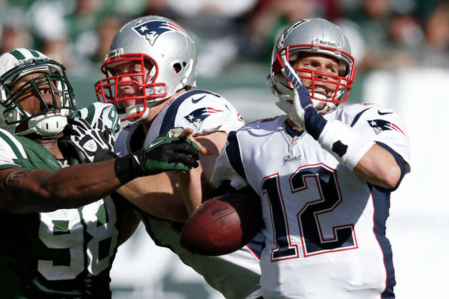 New York Jets outside linebacker Quinton Coples (98) knocks the ball away from New England Patriots quarterback Tom Brady (12) during the second half of an NFL football game Sunday, Oct. 20, 2013, in East Rutherford, N.J. Patriots player at center is unidentified. (AP Photo/Kathy Willens) / AP