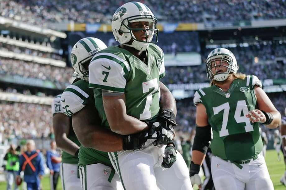 New York Jets quarterback Geno Smith (7) celebrates with New York Jets' Willie Colon (66) and Nick Mangold (74) after rushing for a touchdown during the second half of an NFL football game Sunday, Oct. 20, 2013 in East Rutherford, N.J. (AP Photo/Seth Wenig) / AP