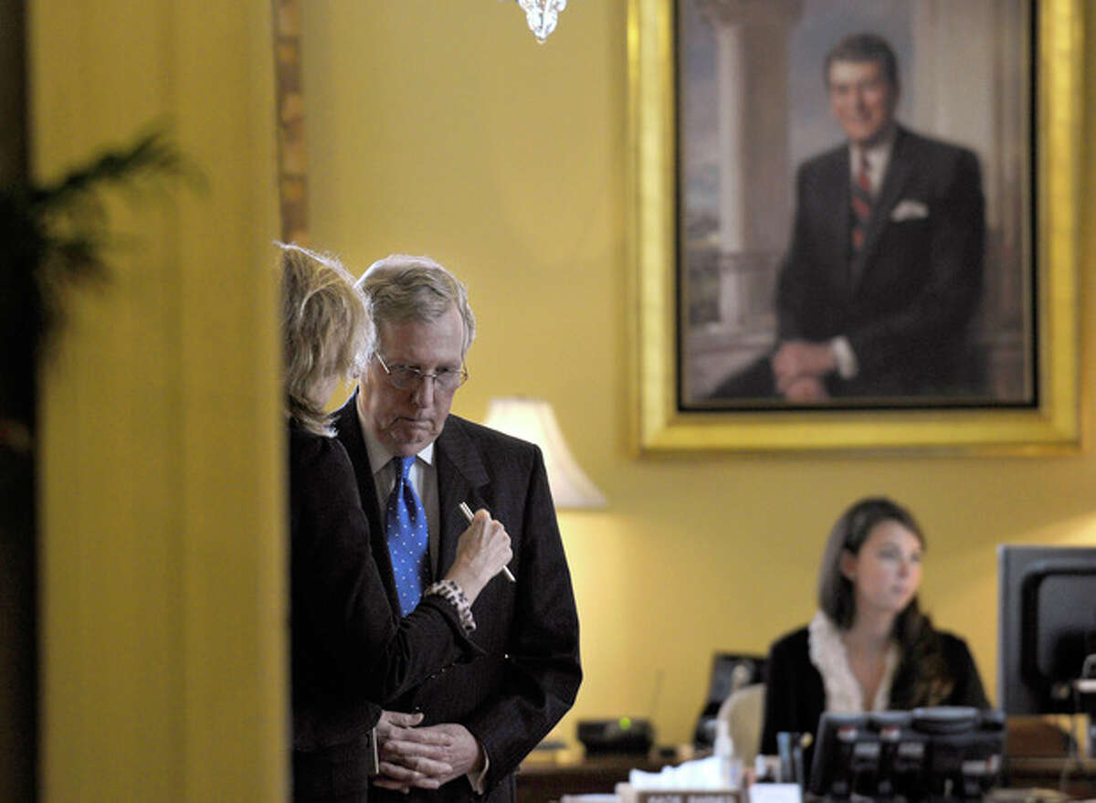 FILE - In this Oct. 9, 2013, file photo Senate Minority Leader Mitch McConnell of Kentucky talks to an unidentified person in his office before a closed-door meeting of Senate Republicans on Capitol Hill in Washington. Results from a recent Associated Press-GfK poll show the Republican leader is catching heat for helping to end the partial federal government shutdown. McConnell agrees with many of his fellow GOP senators that the shutdown was bad strategy and must not be repeated. That puts him on the wrong side of the party?'s tea party wing, and a tea party-backed candidate is challenging McConnell in the primary for his Senate seat. (AP Photo/Susan Walsh, File)