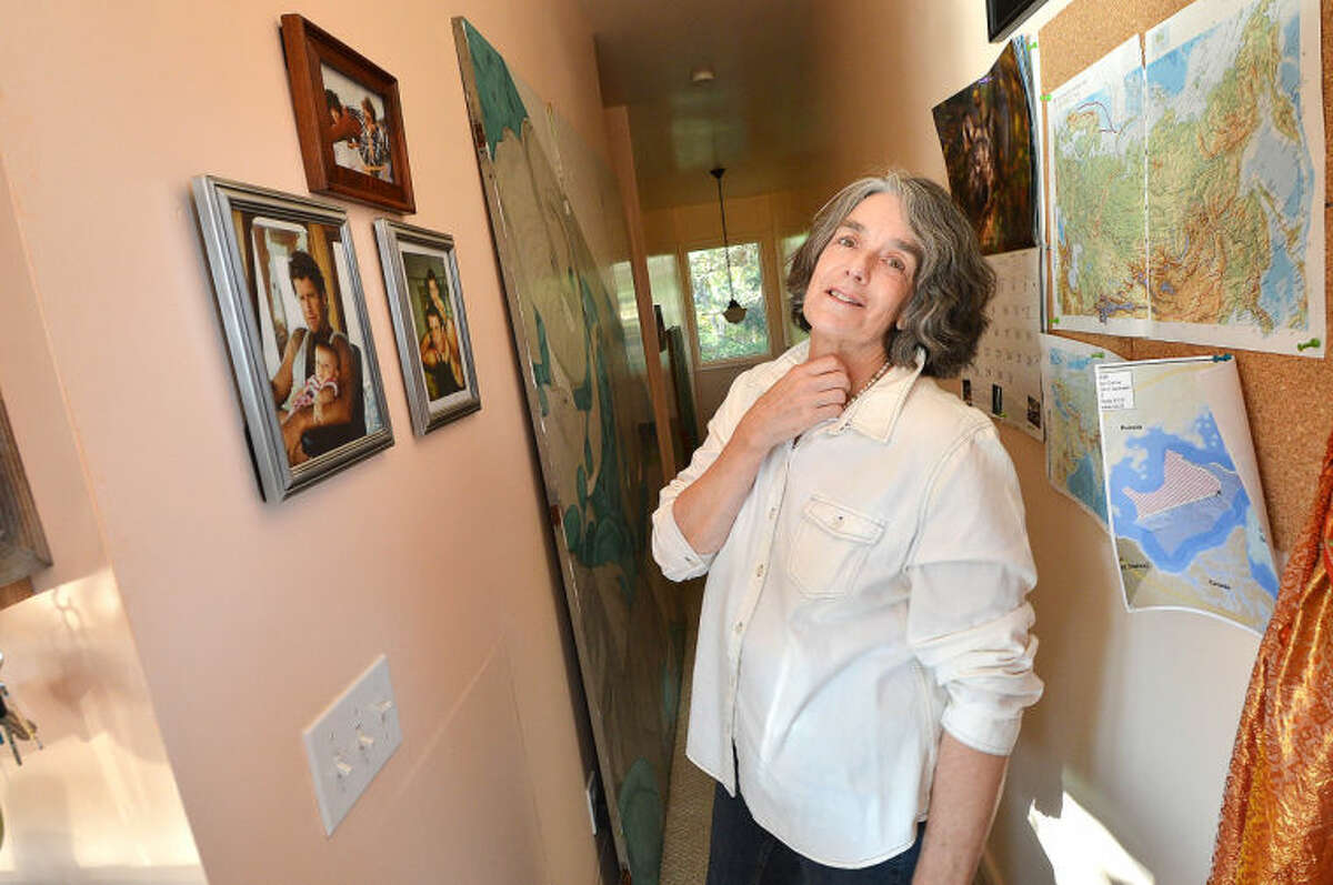 Hour Photo/Alex von Kleydorff . Maggy Willcox looks at photos of her husband Capt Peter Wilcox with his children on the wall of his boyhood home in Norwalk CT.