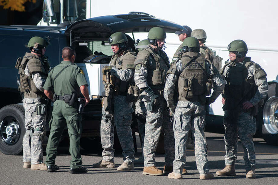 Swat team members secure the scene near Sparks Middle School in Sparks, Nev., after a shooting there on Monday, Oct. 21, 2013. Authorities are reporting that two people were killed and two wounded at the Nevada middle school. (AP Photo/Kevin Clifford) / FR159396 AP