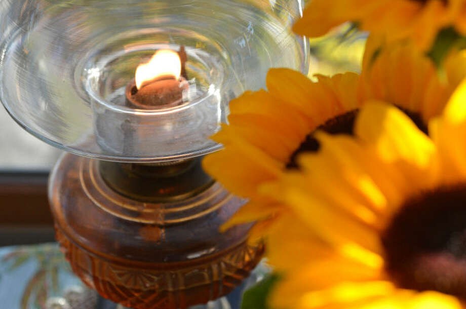 Hour Photo/Alex von Kleydorff. Fresh Sunflowers in a vase next to an oil lamp that is kept burning in hopes of Captain Peter Wilcox' release from Russian detention