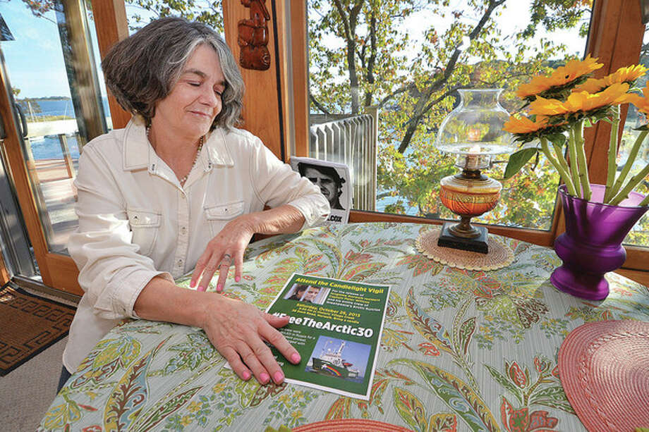 "Hour photos /Alex von KleydorffGreenpeace vessel ""Arctic Sunrise"" Capt. Peter Willcox's wife, Maggy Willcox, sits at a table in his boyhood home in Norwalk, with fresh flowers and an oil lamp kept burning in hope of his release from Russian detention."