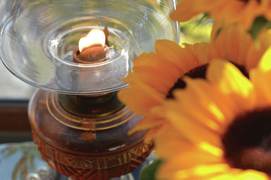 Fresh Sunflowers sit in a vase next to an oil lamp that is kept burning for Capt. Peter Willcox's release.