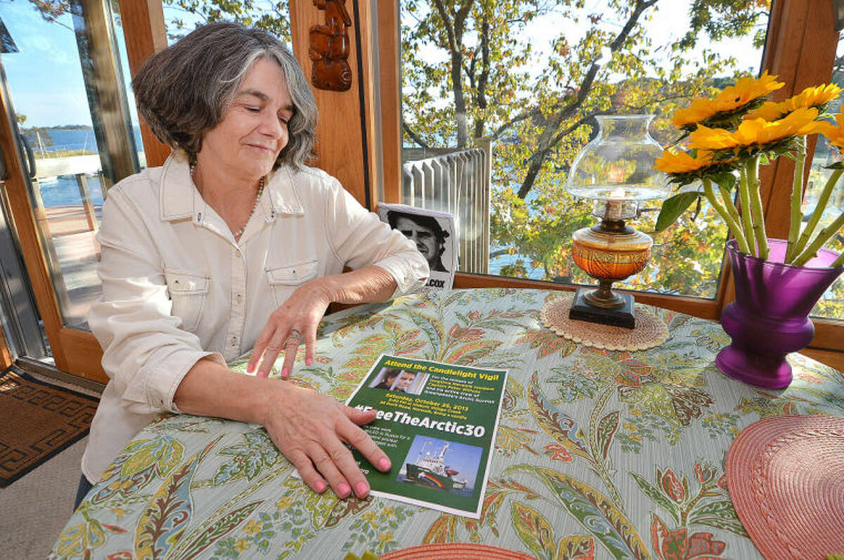 Hour Photo/Alex von Kleydorff . Greenpeace Vessel 'Arctic Sunrise' Captain Peter Willcox's wife Maggy Wilcox sits at a table in his boyhood home in Norwalk ct. With fresh flowers and an oil lamp kept burning in hope of his release from Russian detention.