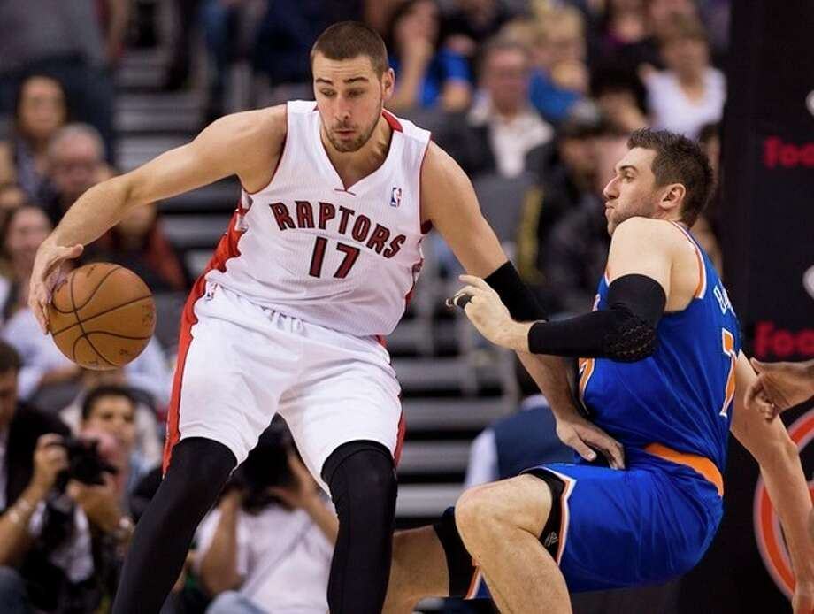 Toronto Raptors forward Jonas Valanciunas (17) knocks down New York Knicks forward Andrea Bargnani, right, during first half NBA pre-season basketball action in Toronto on Tuesday, Oct. 21, 2013. (AP Photo/The Canadian Press, Nathan Denette) / CP