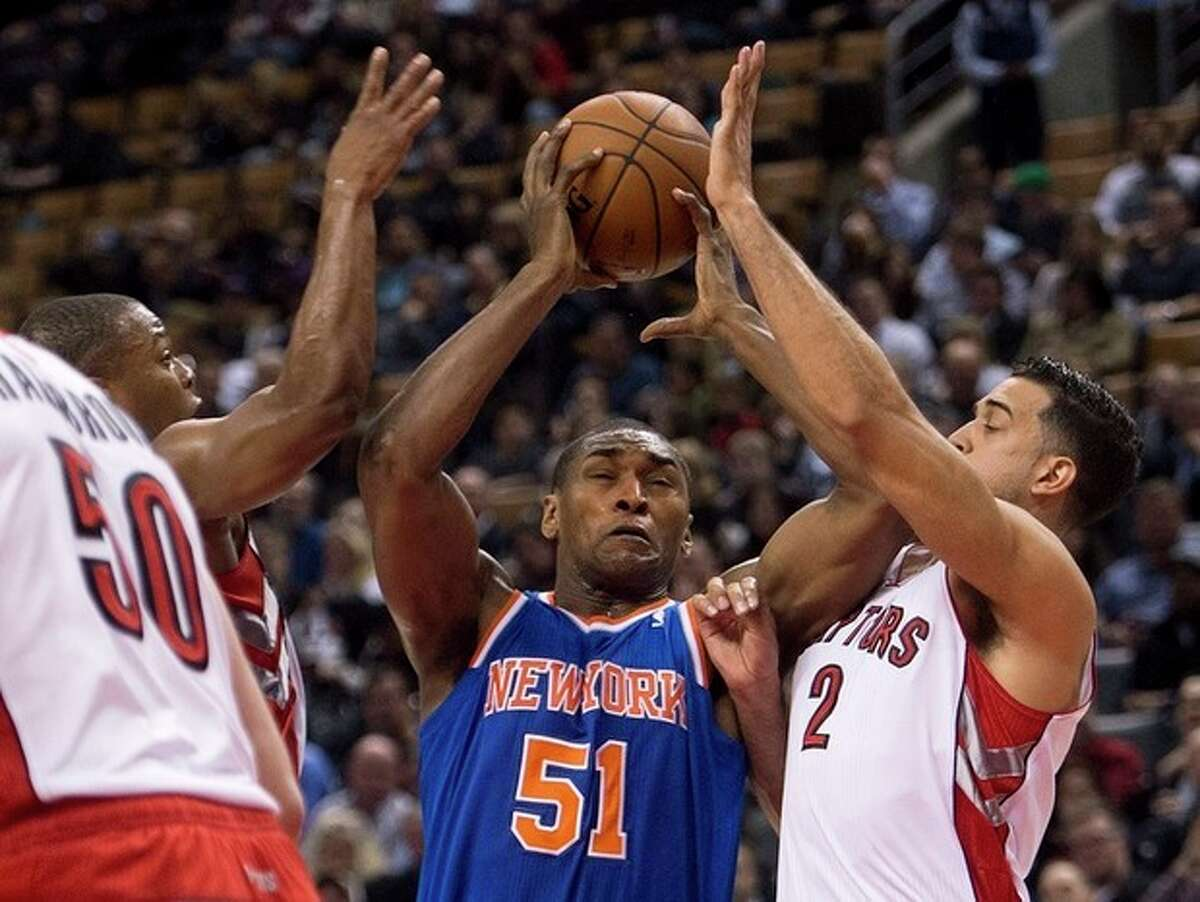 New York Knicks forward Matta World Peace (51) drives past Toronto Raptors forwards Kyle Lowry, left, and Landry Fields, right, during first half NBA pre-season basketball action in Toronto on Tuesday, Oct. 21, 2013. (AP Photo/The Canadian Press, Nathan Denette)