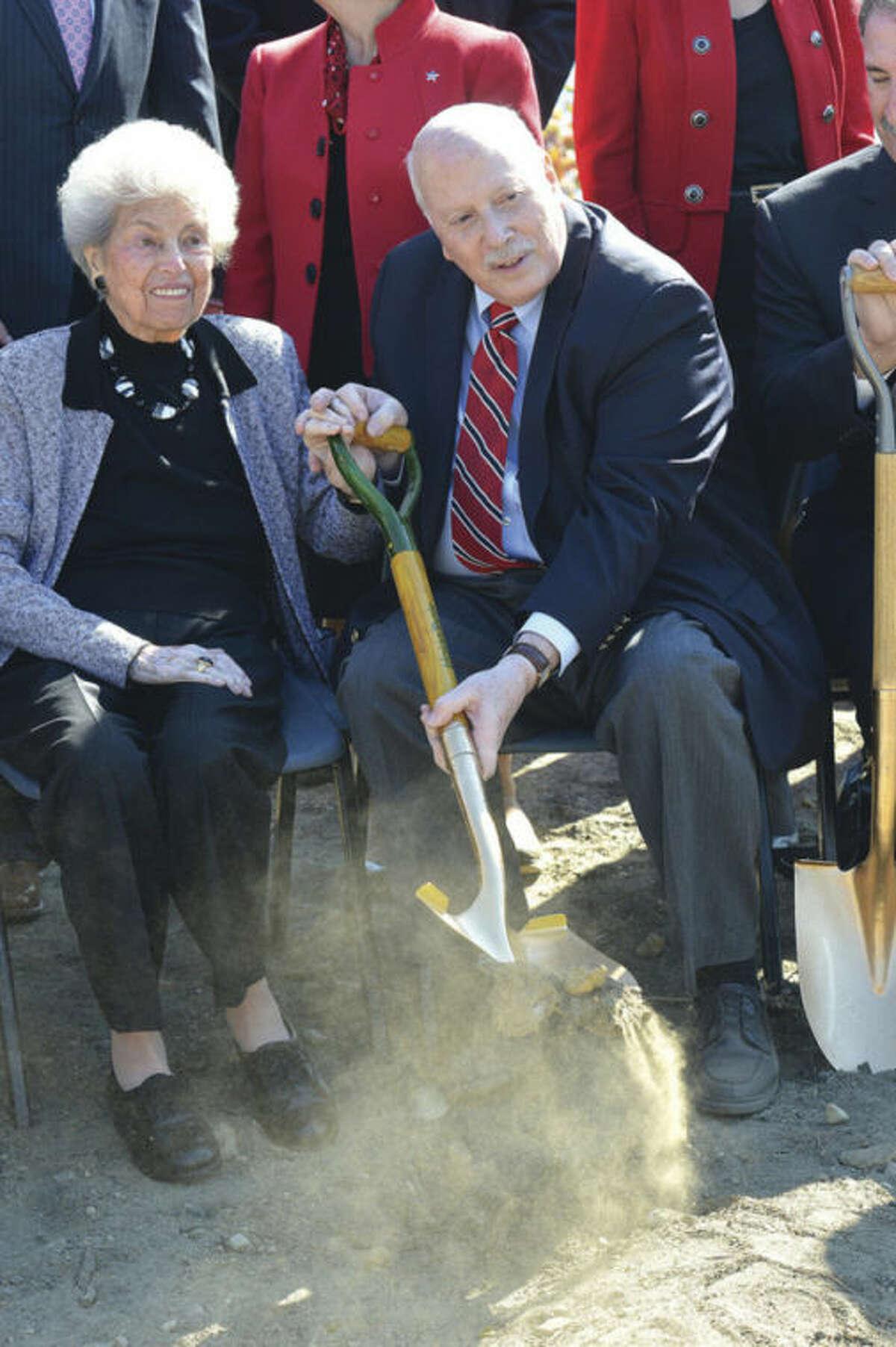 Hour Photo/Alex von Kleydorff . Mimi Levitt and First Selectman Gordon Joseloff grab a shovel of dirt during the groundbreaking ceremony for the Levitt Pavillion for the Performing Arts in Westport.