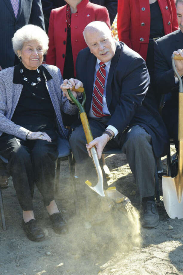 Hour Photo/Alex von Kleydorff . Mimi Levitt and First Selectman Gordon Joseloff grab a shovel of dirt during the groundbreaking ceremony for the Levitt Pavillion for the Performing Arts in Westport.