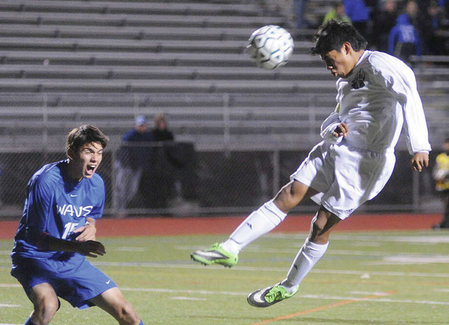 Hour photo/Matthew VinciNorwalk's Jose Canahui, right, takes to the air to head the ball in front of Andrew Mathew of Darien during Monday night's game at Norwalk's Testa Field. The Bears enhanced their chances of earning an FCIAC playoff victory by scoring a 4-1 victory.