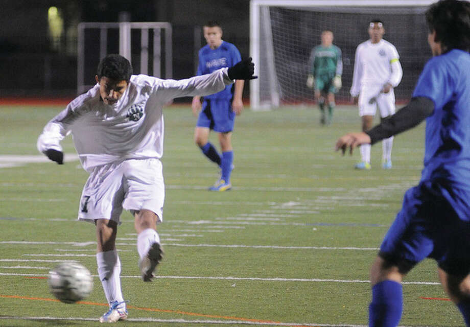 Hour photo/Matthew VinciNorwalk's Patrick Barrantes, left, boots the ball during Monday night's game against Darien. The Bears won. 4-1.