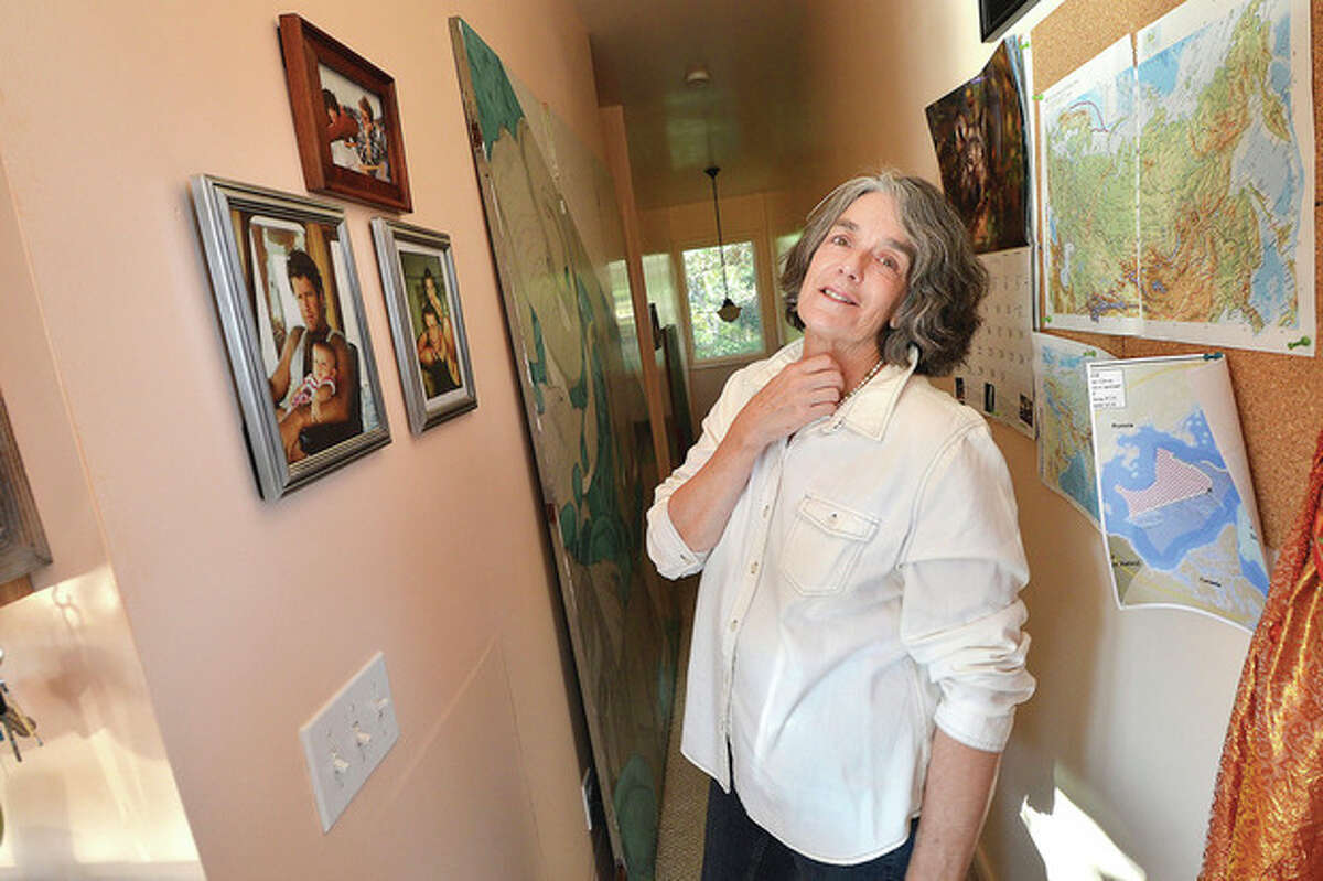 Maggy Willcox looks at photos of her husband, Capt. Peter Willcox, with his children on the wall of his boyhood home in Norwalk.