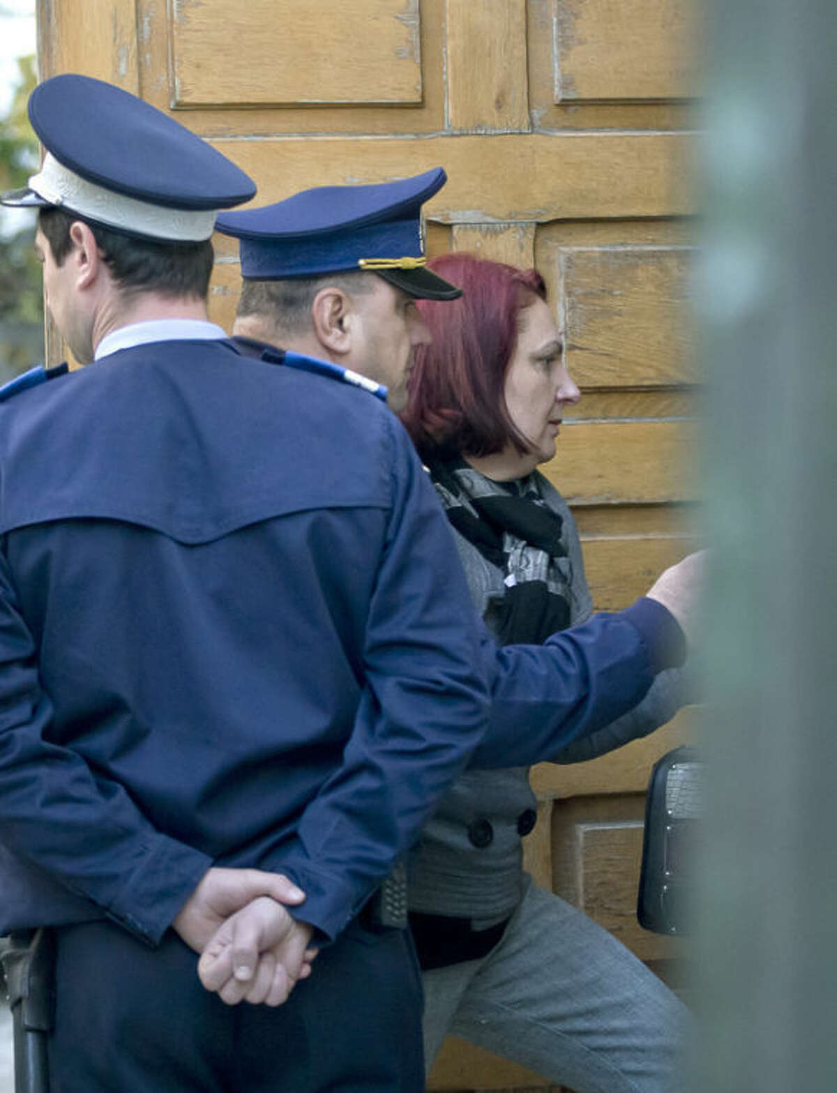 Olga Dogaru, right, the mother of a suspect charged with stealing paintings from a Dutch museum, is escorted into a court building for a hearing in their trial in Bucharest, Romania, Tuesday, Oct. 22, 2013. Three Romanians Radu Dogaru, Alexandru Bitu and Eugen Darie, have pleaded guilty to stealing seven paintings, including works by Picasso, Monet and Matisse, from a Dutch museum in a daring daytime raid that shocked the art world. In their depositions to prosecutors, the suspects said they brought the paintings to Romania, tried to sell them on the black market, then left them with Olga Dogaru, the chief suspect's mother.(AP Photo/Vadim Ghirda)